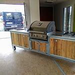 Aussenküche Iron Lärche Dielen mit Napoleon Gasgrill Bilex 485, 4er Gas-Kochfeld von AEG, Edelstahl Arbeitsplatte, Spühle mit Federbrause Mischbatterie, 5 Liter Boiler, 50 Liter Kühlschrank und Platz für 12 kg und 5 kg Gasflasche